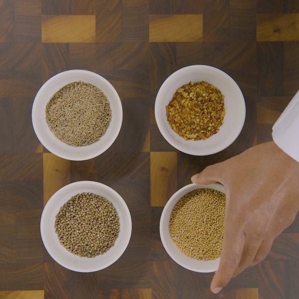 Quatre bols contenant des aromates sont disposés sur un plan de travail.