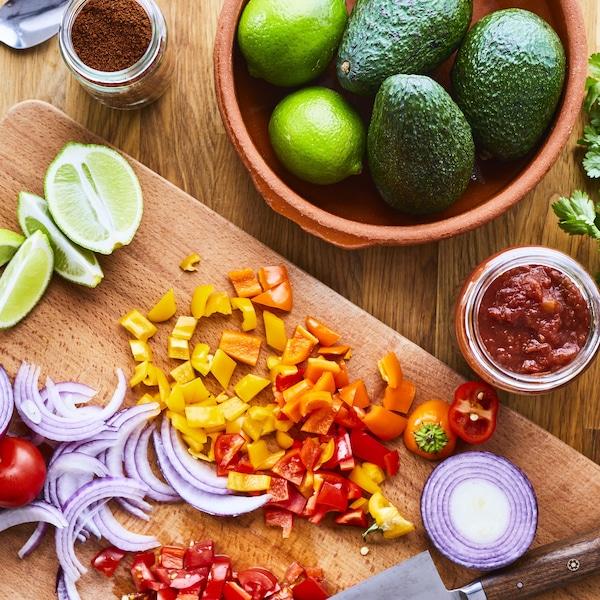 Des limes, des poivrons, des tomates et un oignon rouge coupés sur une planche en bois.