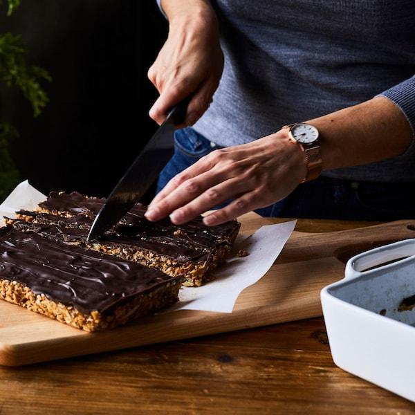 Femme qui tranche des barres tendres maison garnies de chocolat noir.