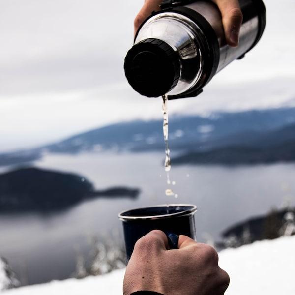 Thermos qui verse une boisson dans une tasse.