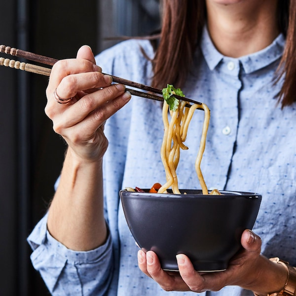 Femme qui tient un bol de nouilles udon.