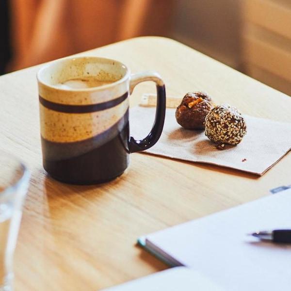 Une tasse de café avec deux boules de collation, disposées sur une table.
