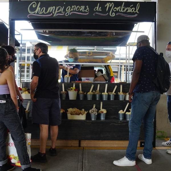 Des gens regardent des champignons présentés sur un étal du marché Jean-Talon