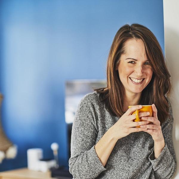 Geneviève O'Gleman tient une tasse à la main et sourit à la caméra.