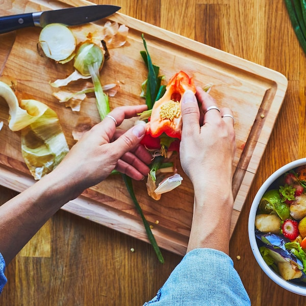 Une personne tranche un poivron sur une planche à découper.