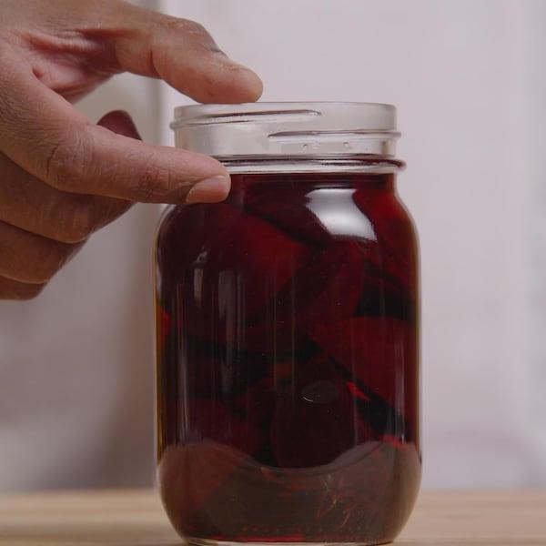Une personne tient un pot en verre contenant des betteraves et s'apprête à visser le couvercle sur celui-ci.