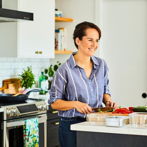 Geneviève O'Gleman qui coupe des légumes sur une planche à découper.