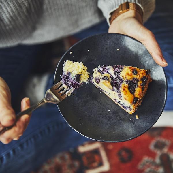 Une personne assise sur un tapis qui mange une part de gâteau aux bleuets.
