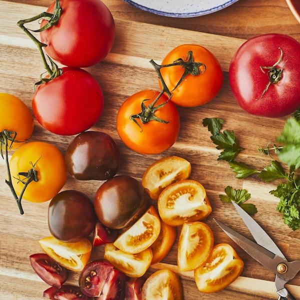 Des tomates et des fines herbes sur une planche à découper