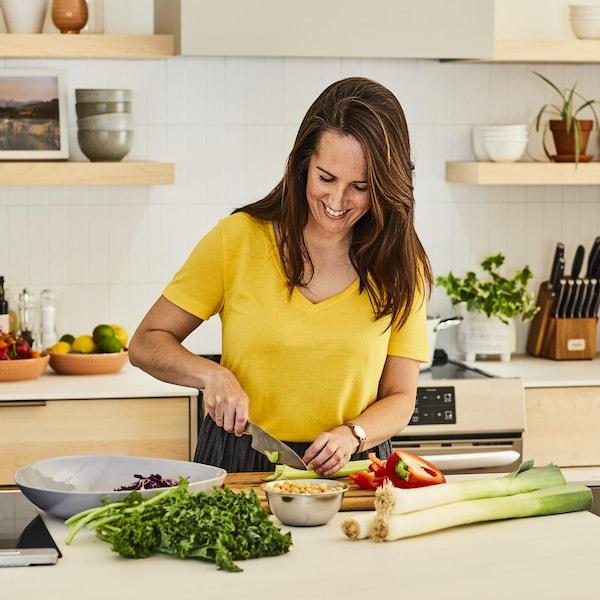 Geneviève O'Gleman coupe des poireaux, des poivrons et du chou sur un ilot de cuisine.
