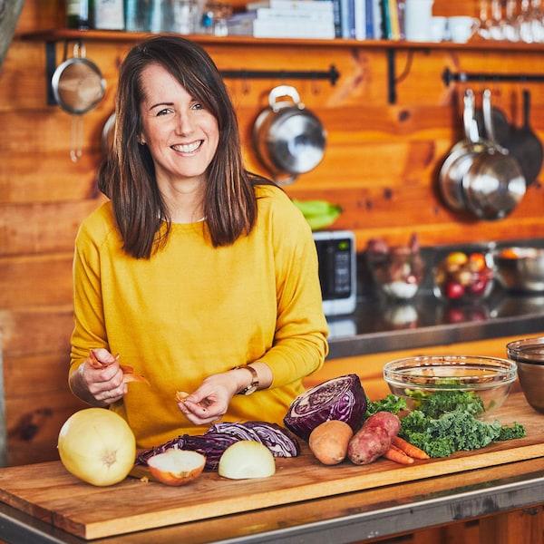 Geneviève O'Gleman dans la cuisine d'un chalet, manipule des légumes sur un ilot en bois.