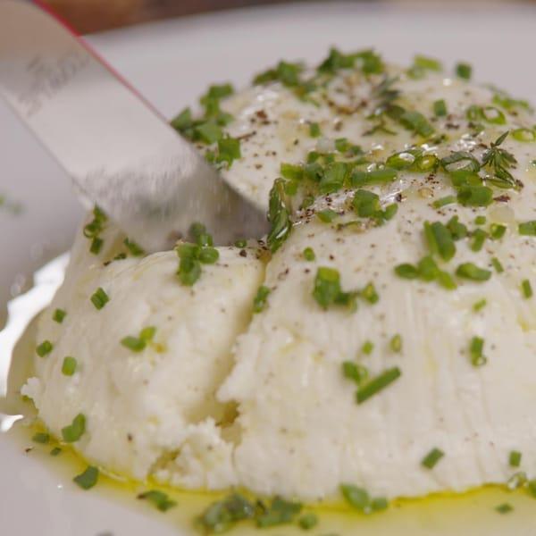 Une personne coupe un morceau de fromage.