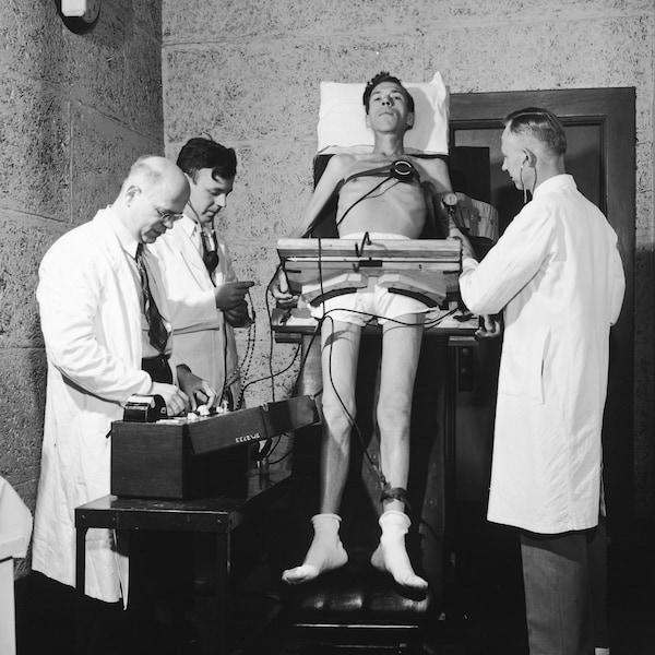 Un homme, d'apparence maigre, est scruté par trois scientifiques et est entouré d'équipements de recherche.