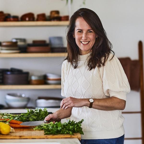 Geneviève O'Gleman qui coupe des légumes sur un grand bloc de bois.