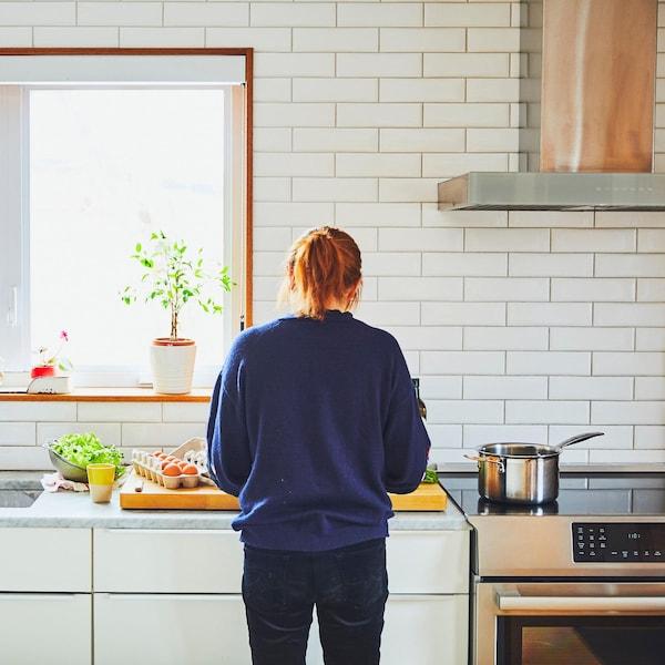 Femme de dos qui prépare le repas au comptoir de cuisine.