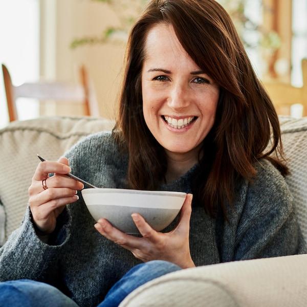 Geneviève O'Gleman assise sur un canapé et qui tient un bol de soupe.