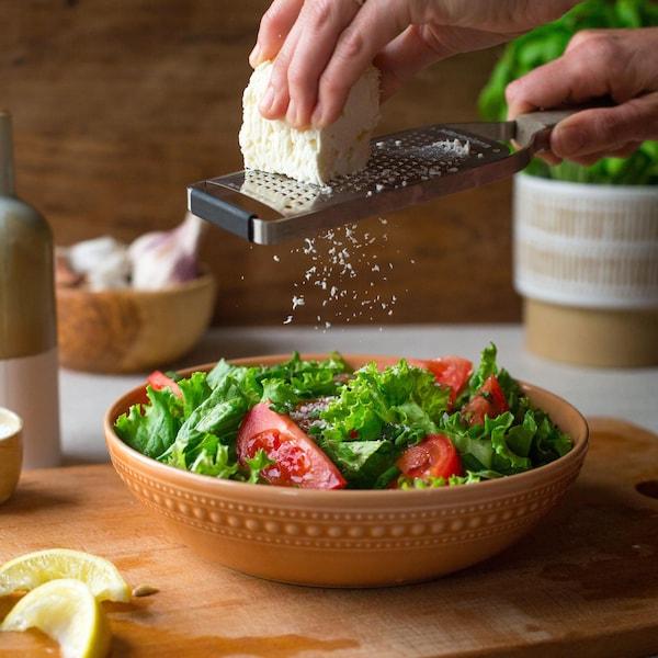 Une personne râpe du fromage feta sur une salade. La portion individuelle est servie dans un bol de terre cuite.