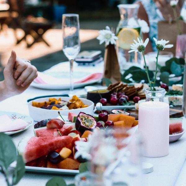 Table à l'extérieur avec des plats de fruits.