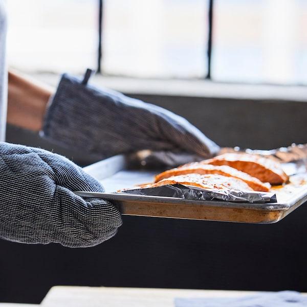 Des pavés de poisson dans une plaque de cuisson qui sort du four.
