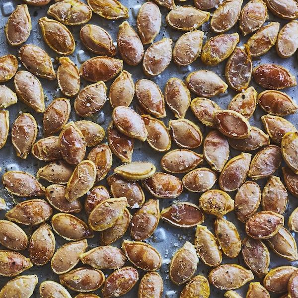 Des graines de citrouille rôties sur une plaque à biscuit vue de haut.