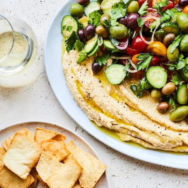 Assiette d'houmous garni d'olives, de tomates, de concombres et de persil.