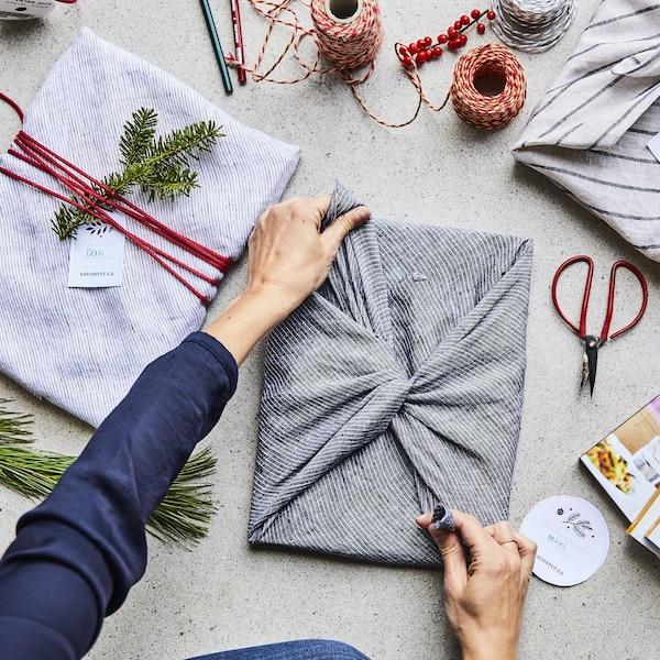 Trois cadeaux emballés dans des linges à vaisselle avec des petites branches de sapin en décoration.