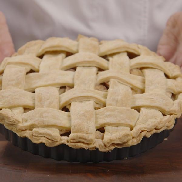 Une personne tient une tarte aux pommes
