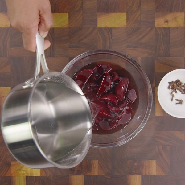 Une personne verse un liquide chaud sur des betteraves.