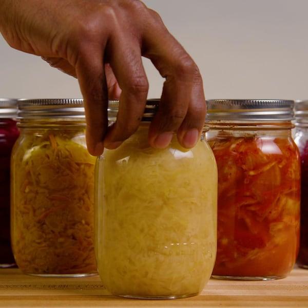 Cinq bocaux contenant des aliments sont en processus de lactofermentation.
