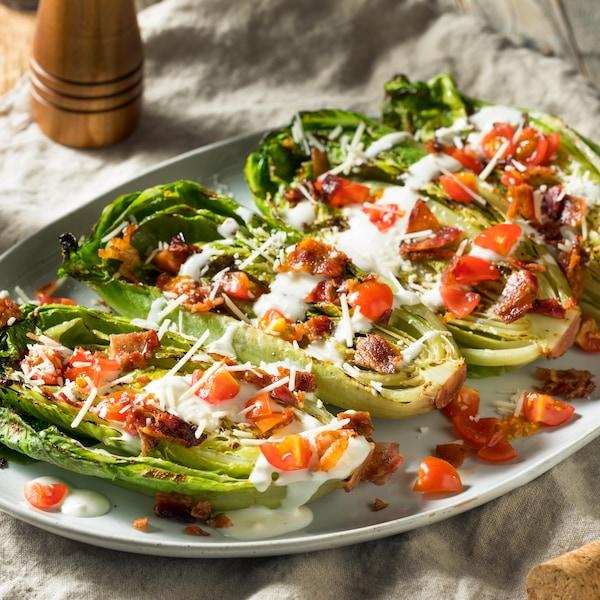Des coeurs de laitue romaine grillée dans une assiette avec des tomates et une vinaigrette.