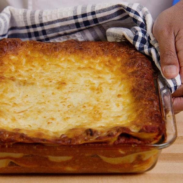 Une personne tient un plat de verre carré contenant une lasagne sortie du four.