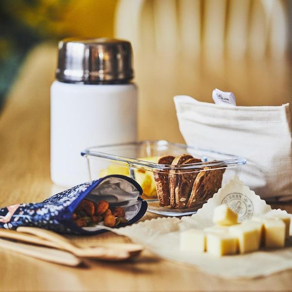 Un thermos, un plat en vert rempli de craquelins, un sac en tissu rempli de noix et des cubes de fromage déposés sur un emballage de cire d'abeille.