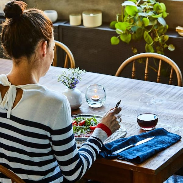 Une femme est assise à table, devant une assiette de salade.