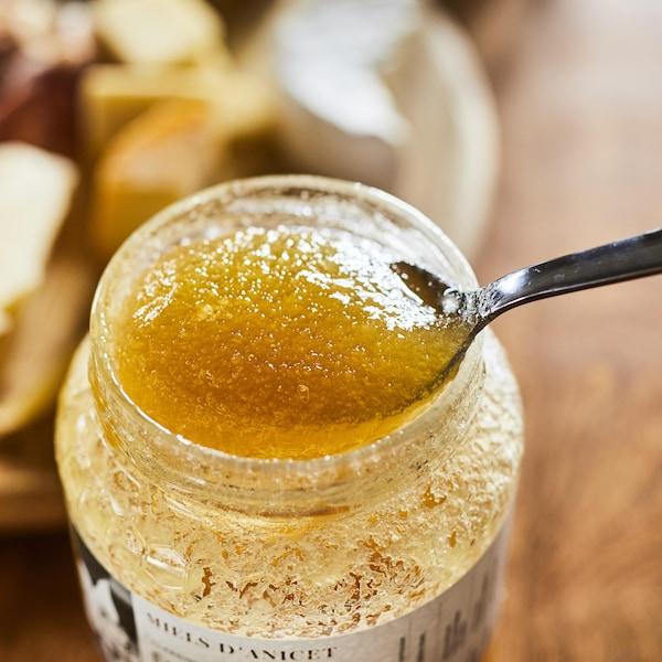 Une cuillère dans un pot de miel qui a commencé à se cristalliser.