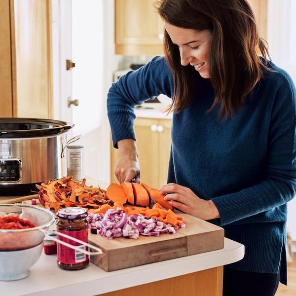 Geneviève O'Gleman qui coupe des légumes pour la mijoteuse.
