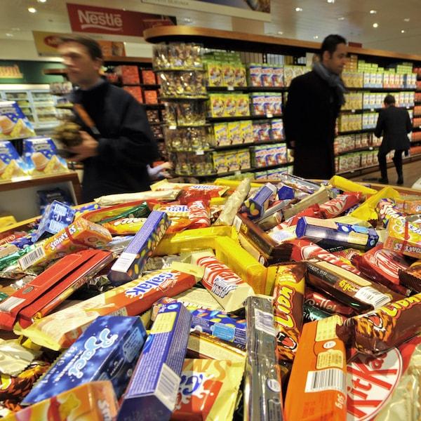 Des barres de chocolat, dont la KitKat, sont présentés sur un étalage.