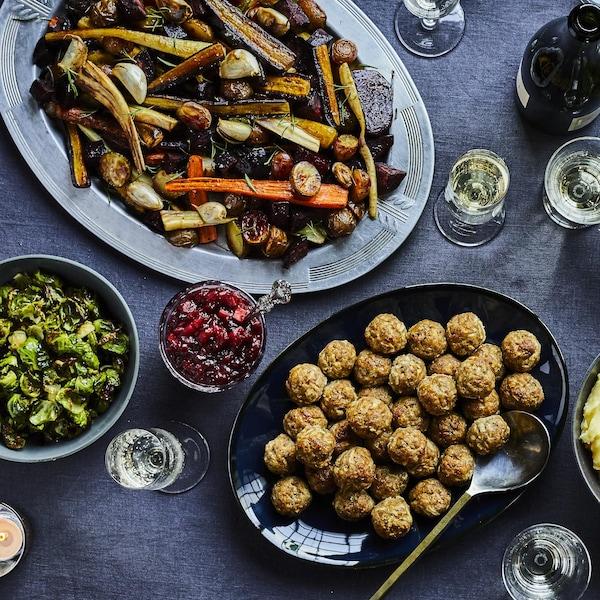 Table festive avec un plat de légumes rôtis, une salade verte, un plat de boulettes de viande et un bol de purée de pommes de terre.