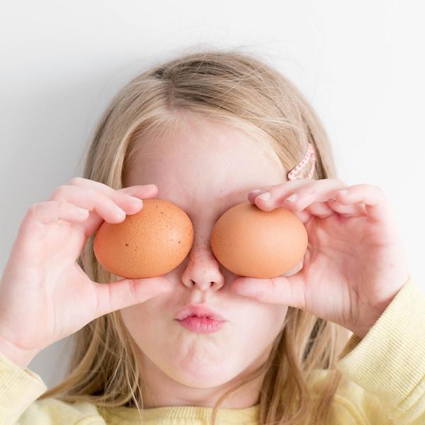 Petite fille qui tient des œufs devant ses yeux.