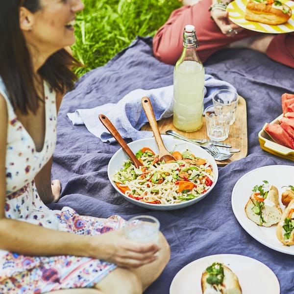 Trois personnes sont assises sur une nappe de pique-nique sur le gazon. Au centre de la nappe, il y a une salade, des quartiers de melon d'eau et des sandwichs de petits pains baguettes.
