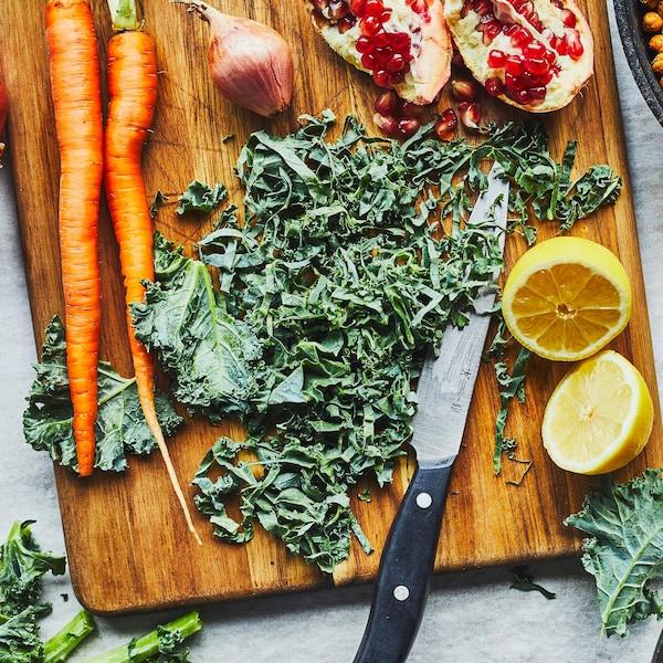 Planche à découper avec du kale, des carottes et une poêlée de pois chiches.