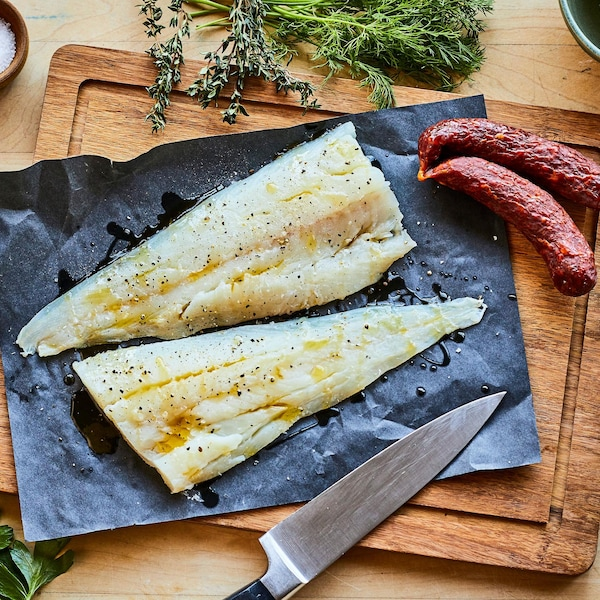Deux filets de poisson, du chorizo posés sur une planche de bois et entourés de fines herbes.