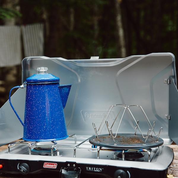 Un réchaud à gaz double est déposé sur une table en bois. Il est ouvert et il y a une bouilloire bleu déposé sur celui-ci.