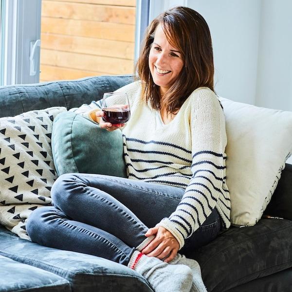 La nutritionniste Geneviève O'Gleman est assise sur un sofa, un verre de vin rouge à la main.