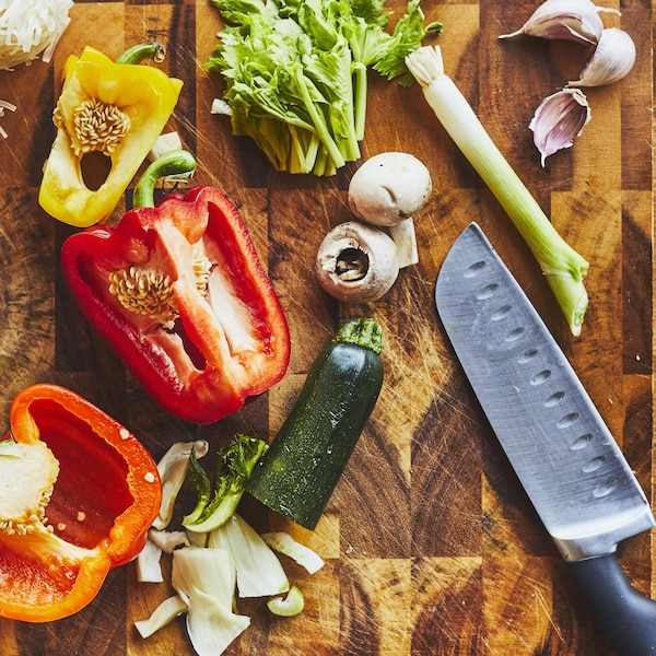 Plusieurs légumes tranchés avec un couteau de chef sur une planche à découper en bois.