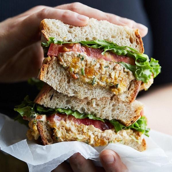 Un sandwich bien garni dans les mains d'une personne.