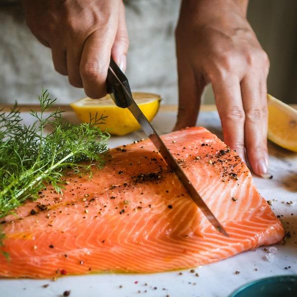 Personne qui tranche un filet de saumon.