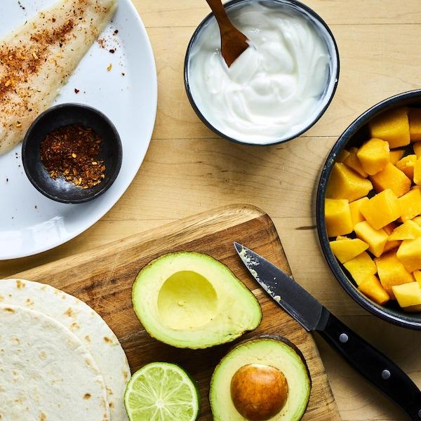 Un filet de poisson blanc cru dans une assiette avec des épices, des tortillas, un avocat, une lime et des cubes de mangue.