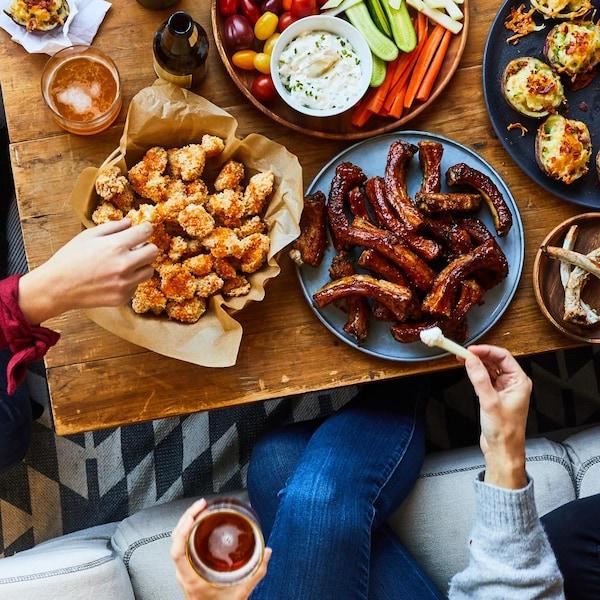 Une table basse vue de haut garnie de bouchées à grignoter et de verres de bière. Des personnes assises autour se servent.