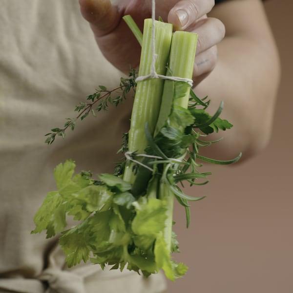 Une personne tient un bouquet garni par le cordon de la ficelle pour montrer le noeud reliant les herbes fraîches.