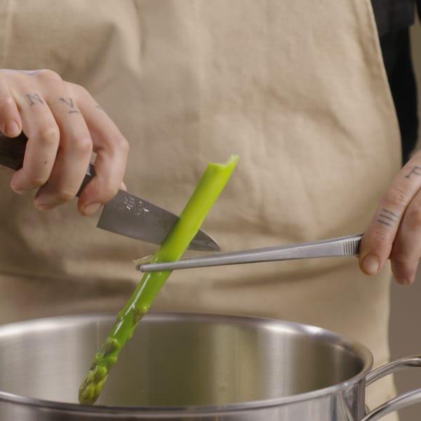 Une personne retire d'un chaudron une asperge pour savoir si elle est cuite.
